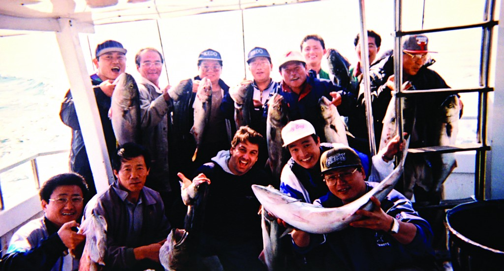 Bobby Egan (C) with a group of North Koreans displaying their catches during a fishing trip off Long Island in 2002. (AP Photo/ Bobby Egan)