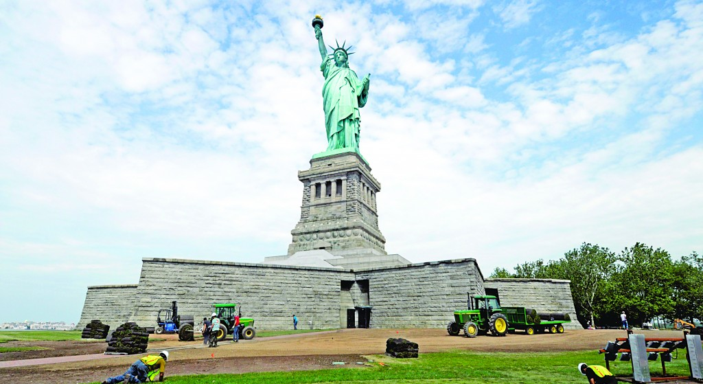 Workers on Liberty Island install sod around the national monument Wednesday in final preparation for its reopening on July 4. (AP Photo/National Park Service)