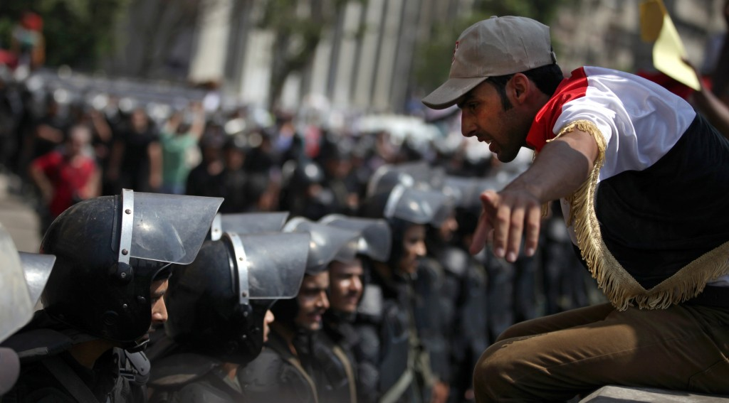 A supporter of Egypt's ousted President Mohammed Morsi talks to riot police standing guard during a demonstration near Tahrir Square in downtown Cairo, Egypt, Wednesday. (AP Photo/Khalil Hamra)