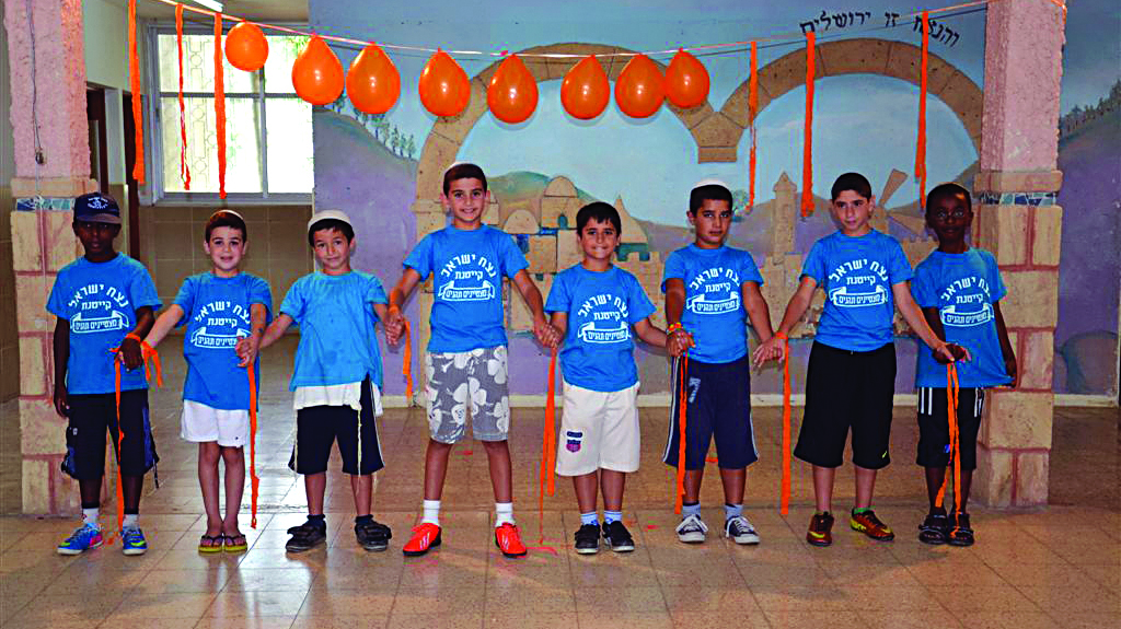 Children who were evacuated from Gush Katif when they were four years old create a human chain with yellow ribbons as part of their learning about the disengagement.