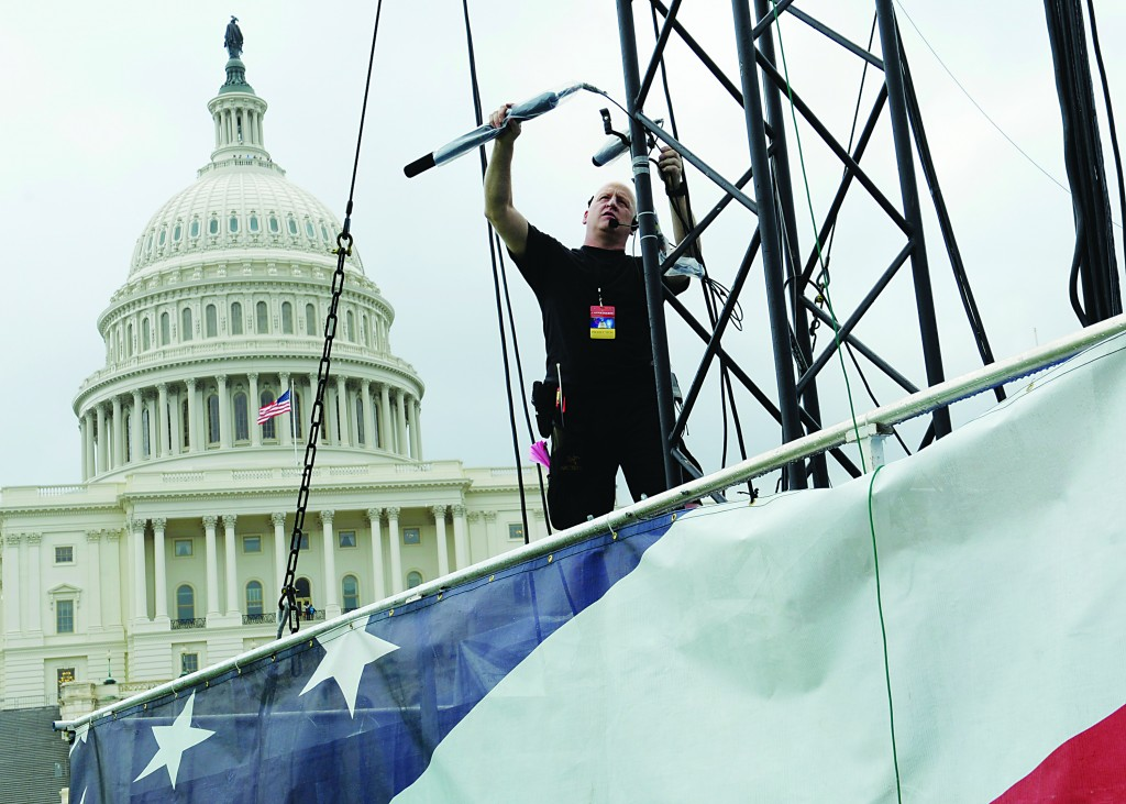 With the Capitol in the background, sound technician Steve Weinkamp of Baltimore puts up a microphone during a dress rehearsal for a fireworks show and concert. As the nation marks 237 years of independence, thousands of Americans were to gather on the National Mall to watch a 17-minute fireworks display. (AP Photo/Susan Walsh)