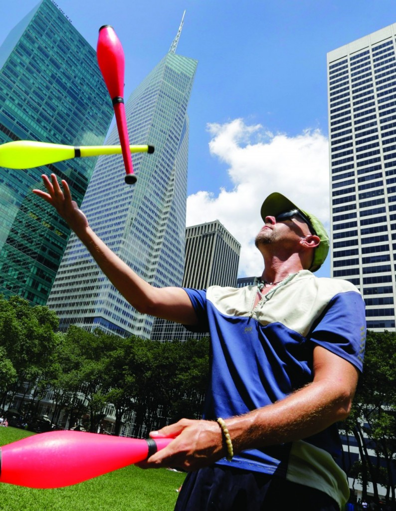 Jeff Mitchell, from Brooklyn, N.Y., practices juggling with clubs in New York's Bryant Park. (AP Photo/Richard Drew)