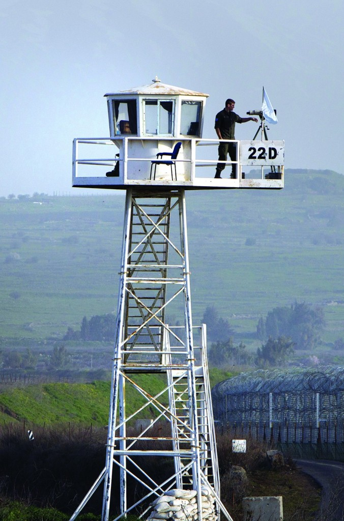 A U.N. peacekeeper stands atop an observation tower in the largely abandoned city of Quneitra in the demilitarized United Nations Disengagement Observer Force (UNDOF) zone, in the Golan Heights. (AHMAD GHARABLI/AFP/Getty Images)