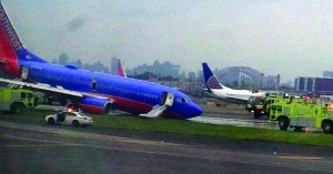The Southwest Airlines plane whose nose gear collapsed as it touched down on the runway, surrounded by emergency vehicles at LaGuardia Airport, Monday. (AP Photo/Jared Rosenstein)