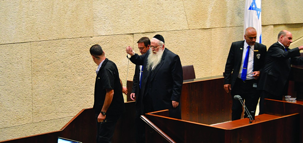 Rabbi Porush being escorted from the Knesset.