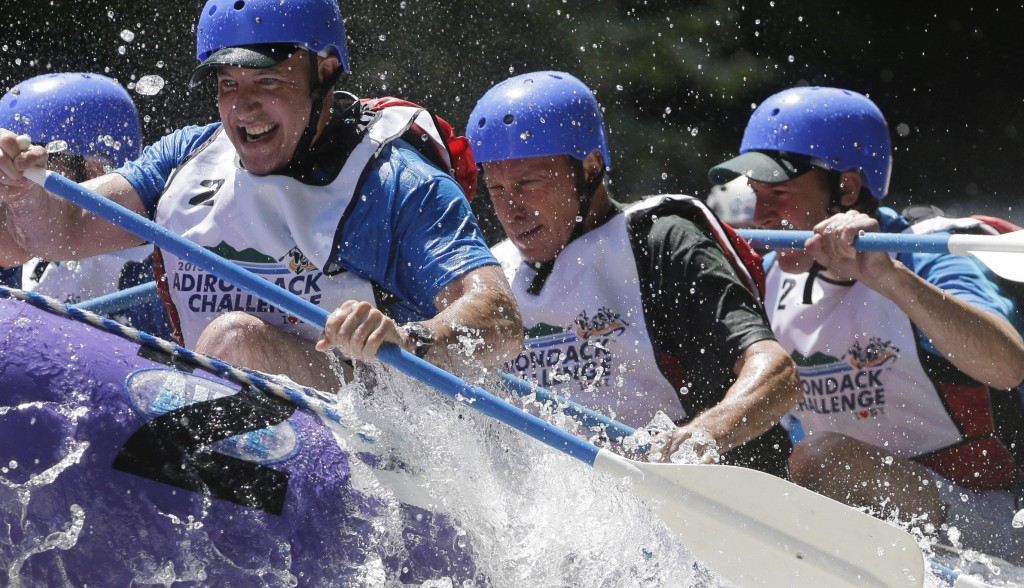 Bloomberg (L) navigates whitewater rapids with his team on the Indian River, as Cuomo (R) gets wet in his team's raft.