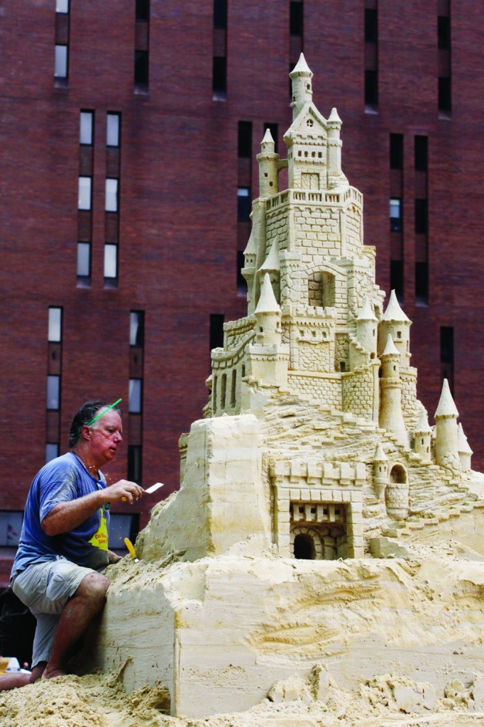 Sculptor Matt Long carves a sand castle in lower Manhattan Monday. The 18-foot-high sculpture takes about three weeks to complete. (AP Photo/Mark Lennihan)
