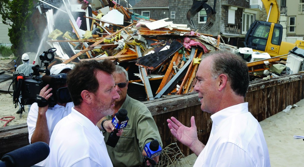 New Jersey Environmental Protection Commissioner Bob Martin (R) talks with homeowner Rich Hennion as Hennion's home, damaged by Superstorm Sandy, is demolished Wednesday in Toms River, N.J. About 3,000 of the estimated 300,000 New Jersey homes damaged by Sandy will be torn down over the summer. (AP Photo/Mel Evans)