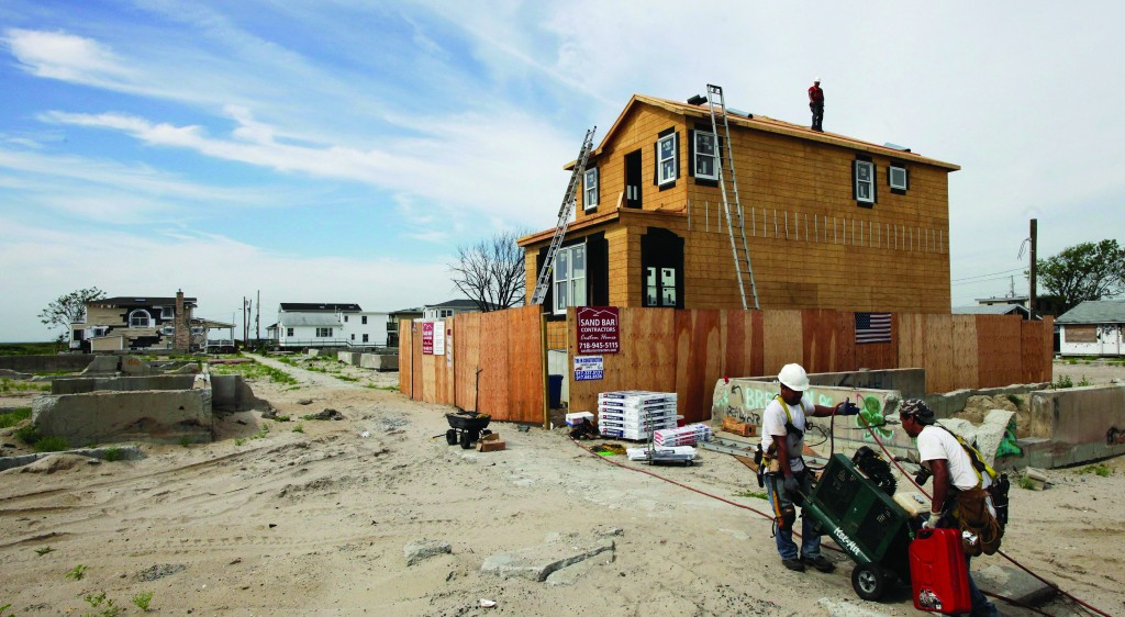 Workers haul equipment to a house construction site in Breezy Point Wednesday, as they start work on the first house to be rebuilt in the beachfront community. More than 110 homes burned to the ground there during Superstorm Sandy. (AP Photo/Mark Lennihan)