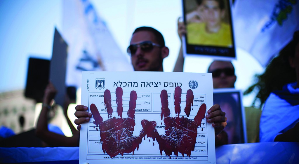 Relatives of Israelis killed in terror attacks hold up signs at a demonstration ahead of the Cabinet vote on Netanyahu's proposal to free 104 Palestinian prisoners as a gesture to Palestinian Authority President Mahmoud Abbas, outside the Prime Minister's Office, on Sunday. (Yonatan Sindel/Flash90)