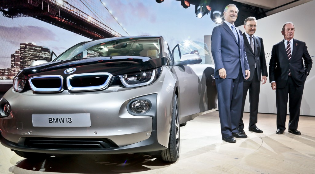 Washington state governor Jay Inslee, left, BMW CEO Norbert Reithofer, center, and New York City Mayor Michael Bloomberg pose next to the new BMWi3 electric vehicle (EV) at its unveiling on Monday, July 29, in New York. (AP Photo/Bebeto Matthews)