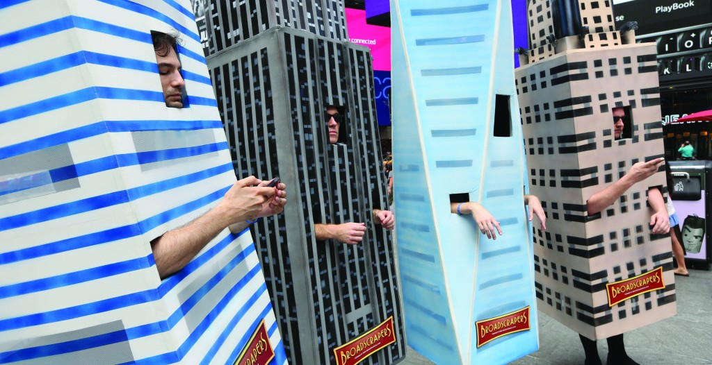 Members sing in Times Square Tuesday as a promotional event for a real estate group. From left, representing Citigroup Center, Empire State Building, 1 World Trade Center and Chrysler Building. (AP Photo/Mary Altaffer)