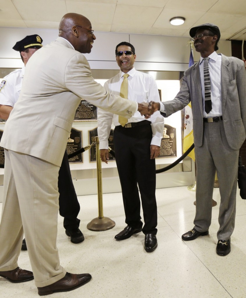 Port Authority Deputy Director Stephen Kingsberry (L) acknowledges Lalit Moorjani (C) and Stanley Eady at the Journal Square PATH train station Wednesday in Jersey City, N.J. (AP Photo/Julio Cortez)
