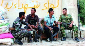 Free Syrian Army fighters chat as they sit together along a street in Ashrafieh, Aleppo. (REUTERS/Aref Hretani)