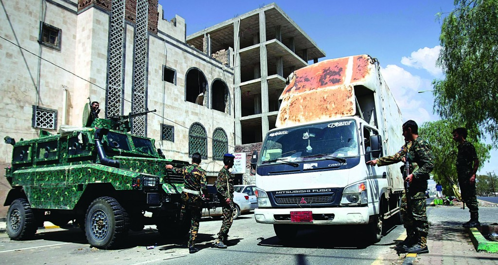 Yemeni soldiers stop a truck at a checkpoint on a street leading to the U.S. and British embassies in Sanaa, Yemen, Saturday. (AP Photo/Hani Mohammed)