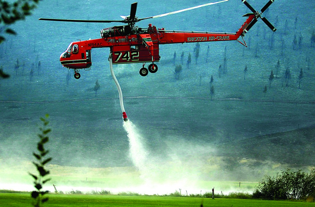 A helicopter descends to refill with water from a pond while battling the Beaver Creek Fire north of Hailey, Idaho, on Saturday. (AP Photo/Times-News, Ashley Smith)