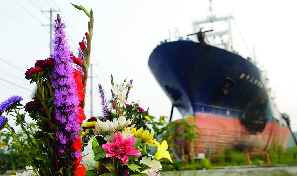 In this photo taken on Sunday, flowers are left by a stranded fishing boat, which has become a symbol of the devastation of the 2011 tsunami in the northeastern coastal city of Kesennuma. The stranded fishing boat is being torn down. (AP Photo/Azusa Uchikura)