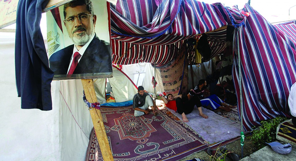 Supporters of Egypt's ousted President Mohammed Morsi, seen in the poster, rest in a tent in a protesters' camp in front of Cairo University in Giza, southwest of Cairo, Egypt, on Thursday. (AP Photo/Amr Nabil)