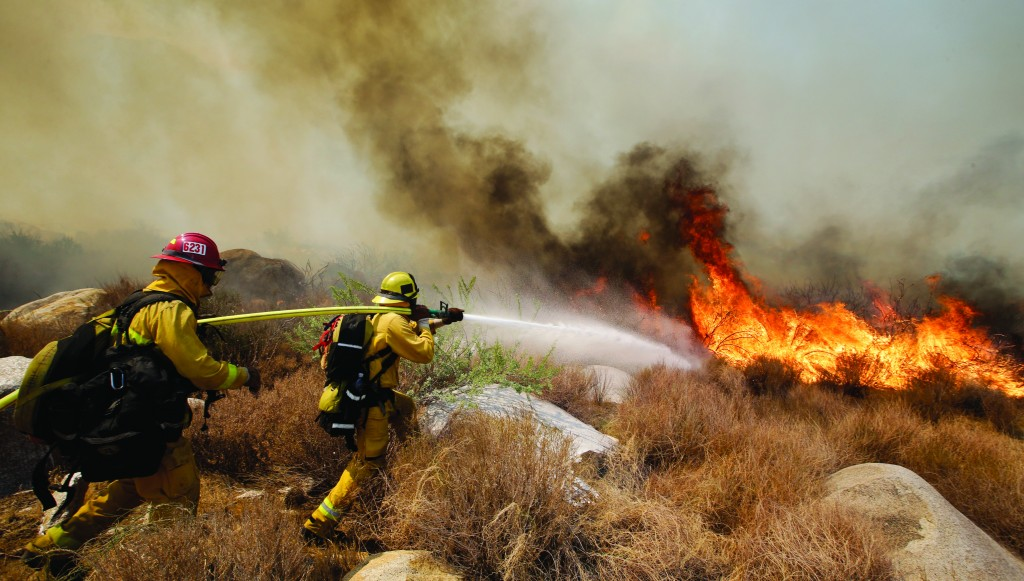 Firefighters battle a wildfire on Thursday in Cabazon, Calif. (AP Photo/Jae C. Hong)