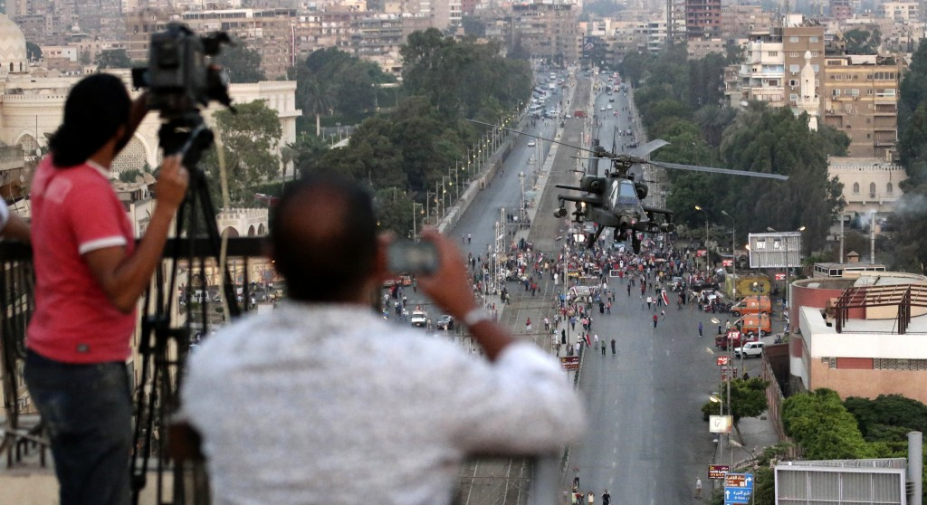 In this July 5 file photo, journalists film an Egyptian military attack  helicopter as it flies by the Presidential palace, in Cairo, Egypt. An Egyptian journalist shot to death by soldiers at a checkpoint raises to 5 the number of journalists killed in the past week across Egypt.  (AP Photo/Hassan Ammar)