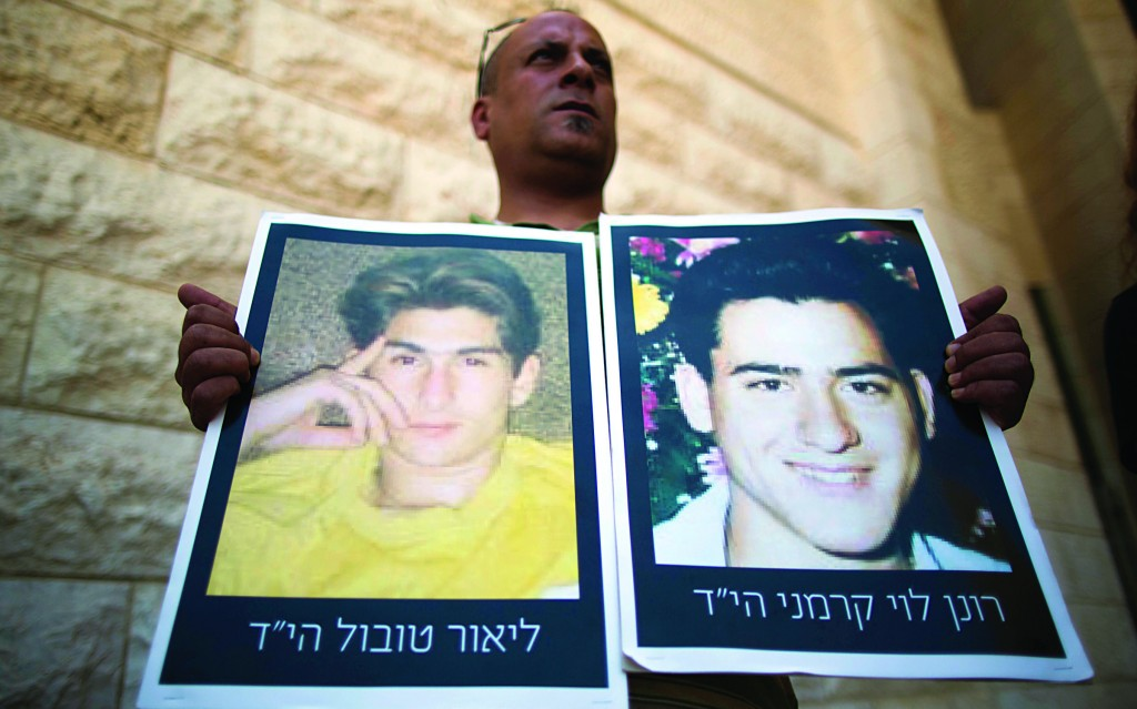 A relative of Israelis killed in terror attacks holds a sign during a demonstration outside the High Court in Yerushalayim on Sunday. (Yonatan Sindel/Flash90)