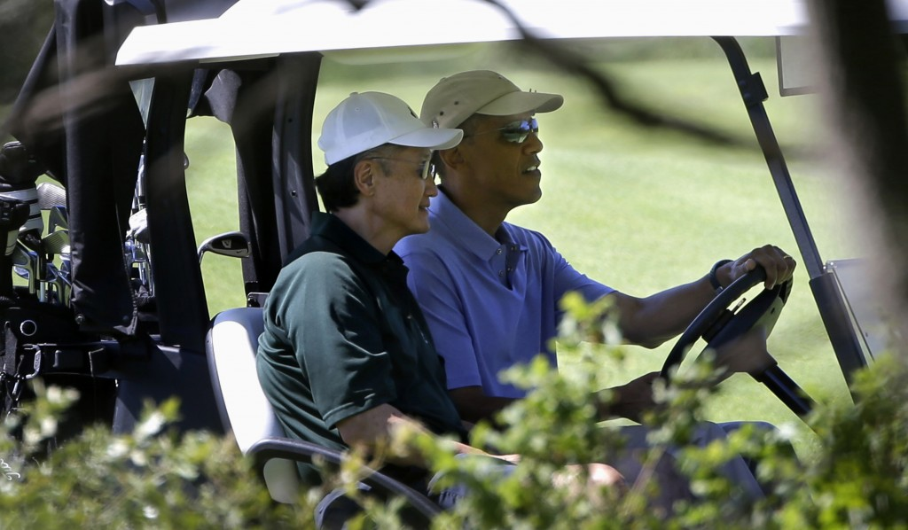 President Barack Obama drives a golf cart with World Bank President Jim Kim during a golf outing at Vineyard Golf Club in Edgartown, Mass., on the island of Martha's Vineyard on Wednesday. (AP Photo/Steven Senne)