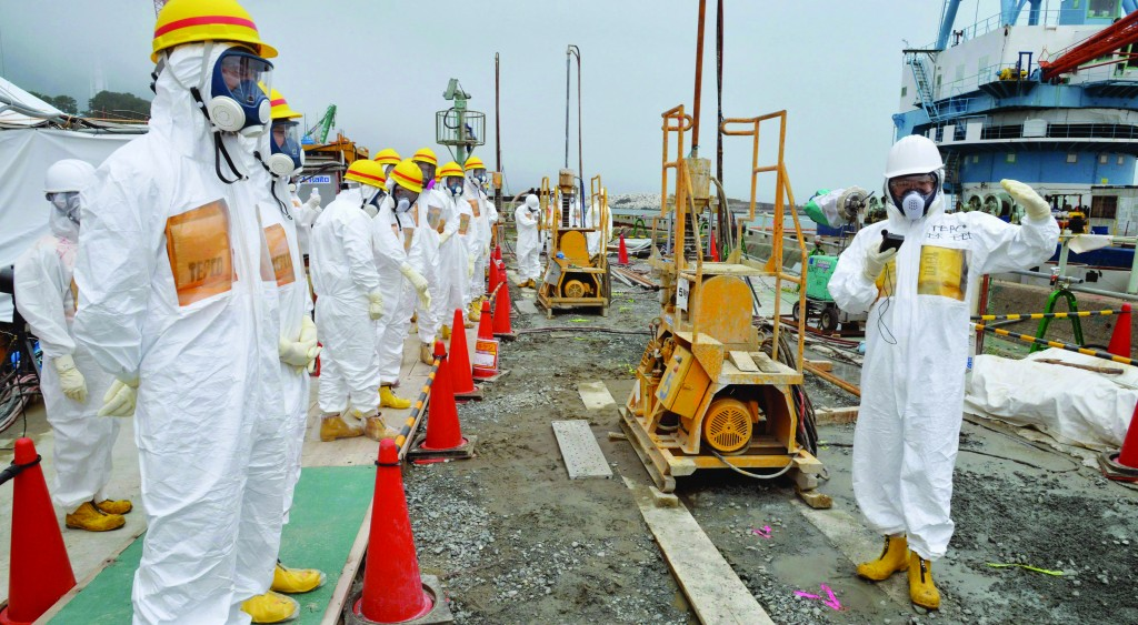 Officials and experts from local towns inspect a coastal embankment where contaminated water leaks occur near Fukushima Dai-Ichi nuclear plant Units 1 and 2 of Tokyo Electric Power Co., in Okuma, Fukushima prefecture, northeastern Japan. (AP Photo/Kyodo News)