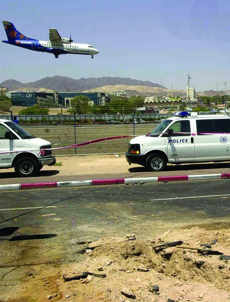 In this file photo taken Aug. 19, 2005, a crater left by a rocket is seen on the side of the road near the airport of southern Israel's resort town of Eilat. (AP Photo/Yheuda Ben Ipah, File)