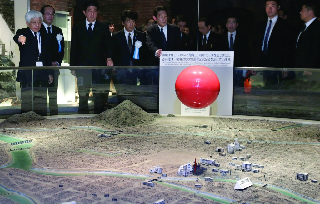Japanese Prime Minister Shinzo Abe, third from left, accompanied by Hiroshima Peace Memorial Museum Director Kenji Shiga, left, looks at a diorama of Hiroshima city after the Aug. 6, 1945 atomic bombing, at Hiroshima Peace Memorial Museum in Hiroshima, western Japan, on the 68th anniversary the bombing. (AP Photo/Shizuo Kambayashi)