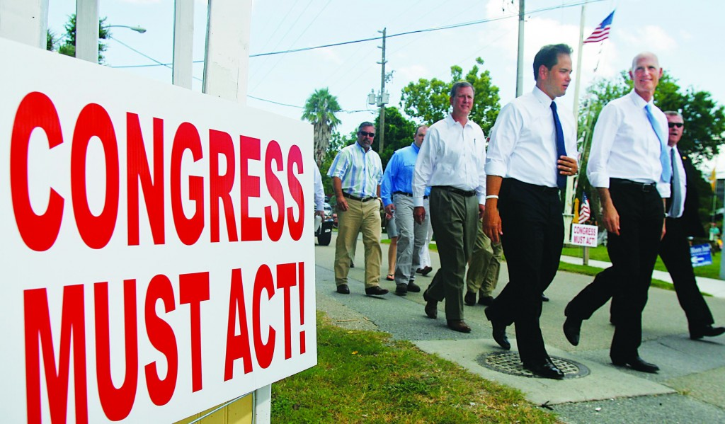 U.S. Sen. Marco Rubio (C) and Florida Gov. Rick Scott walk past a sign on Water St. Tuesday in Apalachicola, Fla. (AP Photo/Phil Sears)
