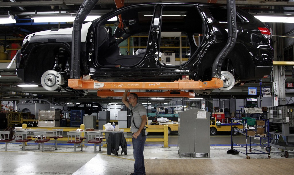 In this May 8, 2013, file photo, Jeff Caldwell, 29, right, a chassis assembly line supervisor, checks a vehicle on the assembly line at the Chrysler Jefferson North Assembly plant in Detroit. (AP Photo/Paul Sancya, File)