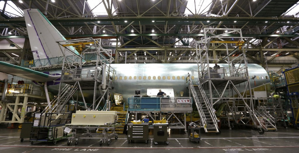 In this photo taken Wednesday, May 29, 2013, a Boeing 777 jet is partially surrounded by scaffolding while being assembled at the company's production plant in Everett, Wash. (AP Photo/Elaine Thompson)