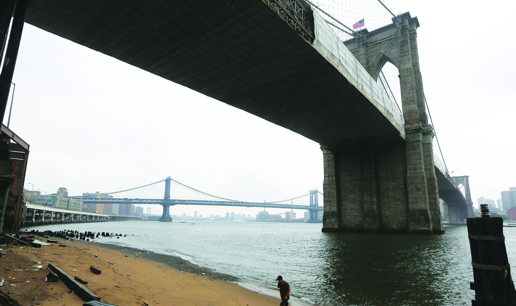 A man walks on the East River beach under the Brooklyn bridge Thursday, which a $7 million plan would transform into a recreational destination. (AP Photo/Mary Altaffer)