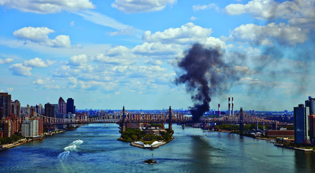 A cloud of smoke billows from the Queensboro Bridge in New York on Friday. (AP Photo/Frank Ritter)