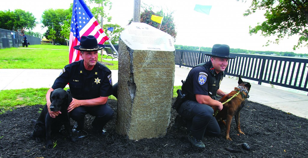 Erie County Sheriff's Dept. Captain Sean Simet with Jules (L), and Deputy Jordan Graber with Cort, attend the dedication of a stone memorial honoring dogs that served in K-9 units in Buffalo, N.Y., on Tuesday. (AP Photo/The Buffalo News, John Hickey)