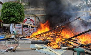 Makeshift wooden huts burn at a sit-in camp set up by supporters of ousted Islamist President Mohammed Morsi, as Egyptian security forces clear the camp near Cairo University in Cairo's Giza district, Egypt, Wednesday. (AP Photo/Mohammed Asad)
