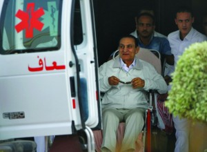 Former Egyptian President Hosni Mubarak, 85, is escorted by medical and security personnel into an ambulance on Sunday.(AP Photo/Amr Nabil)