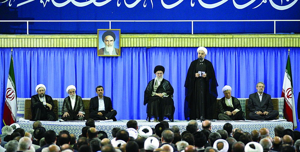 President-elect Hasan Rouhani (3rd R) speaks in an endorsement ceremony led by Supreme Leader Ayatollah Ali Khamenei (C) in Tehran, Iran, Saturday. A portrait of late revolutionary founder Ayatollah Khomeini hangs in background. (AP Photo/Office of the Iranian Supreme Leader)
