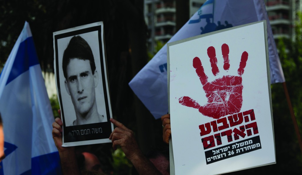 Relatives of Israelis killed in terror attacks holding signs as they protest against the release of some 26 Palestinians prisoners, in Tel Aviv on Monday. (Flash90)