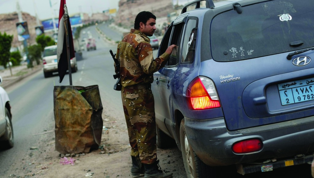 A Yemeni soldier inspects a car at a checkpoint on a street leading to the U.S. embassy in Sanaa, Yemen, Sunday. (AP Photo/Hani Mohammed)