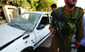 An Israeli soldier walks past a car damaged by a barrage of Lebanese rockets fired at Israel, in Kibbutz Gesher HaZiv, near the northern city of Nahariya on Thursday. (REUTERS/Ronen Zvulun)