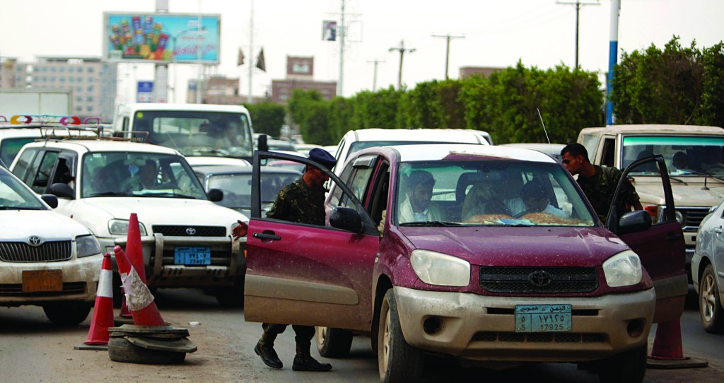 Police troopers check cars at a checkpoint on the road leading to the Sanaa International Airport Tuesday. (.REUTERS/Khaled Abdullah)