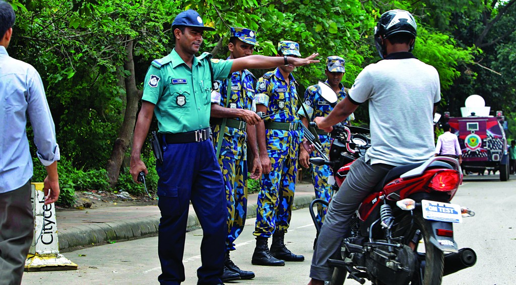 Bangladeshi police stop a motorist in front of the U.S. Embassy, which remained closed due to a security threat in Dhaka, Bangladesh, Sunday. (AP Photo/A.M. Ahad)