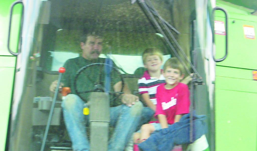 David Krenzer operating the combine on his farm with his two grandsons. (Save Krenzer Farm)