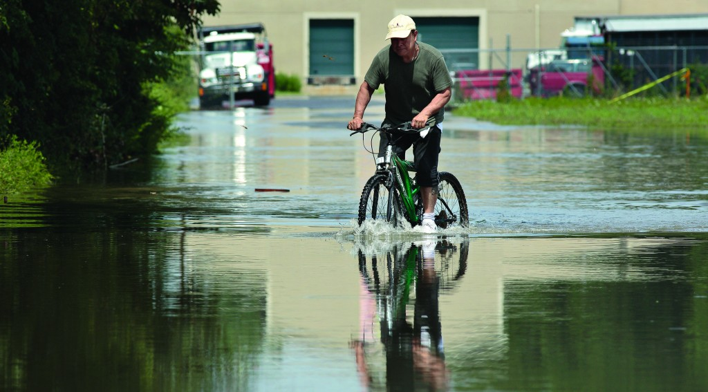 Julio Trujillo pedals through flooding in Middletown, N.Y., on Friday. (AP Photo/Times Herald-Record, Tom Bushey)