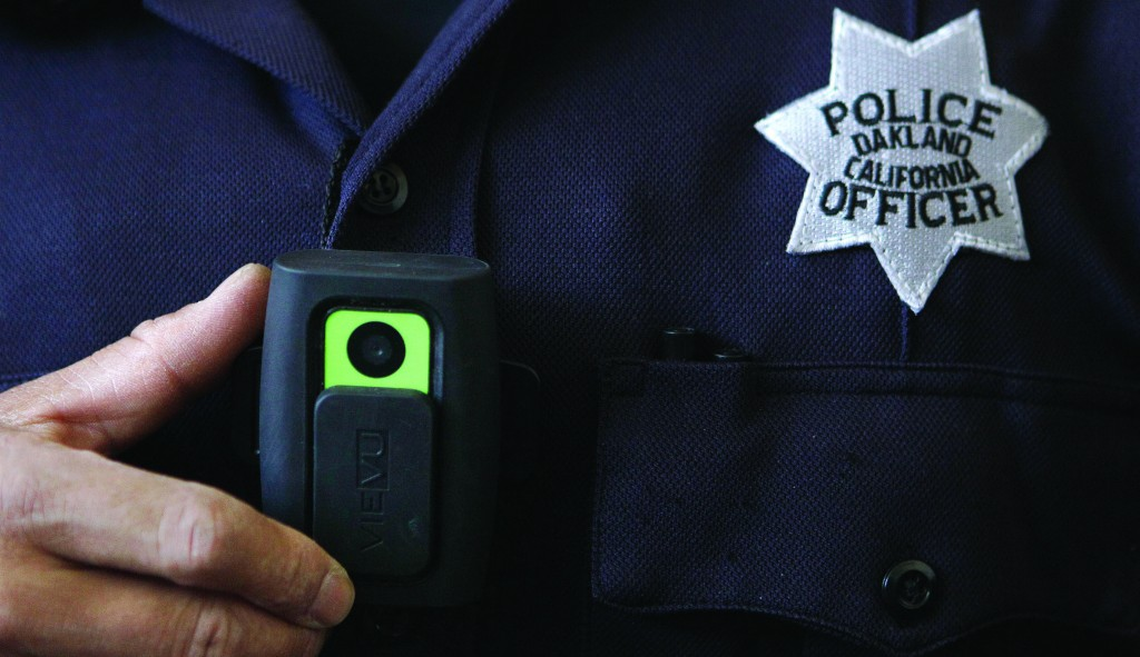An Oakland, Calif., police officer shows a video camera worn by some officers. (AP Photo/Jeff Chiu)