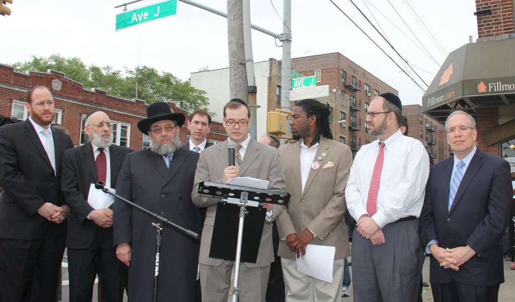 """Officials attend the ceremony renaming the corner of Avenue J and Nostrand """"Yoseph Robinson Avenue,"""" after the ger tzedek who was killed several feet away. (Shimon Gifter)"""