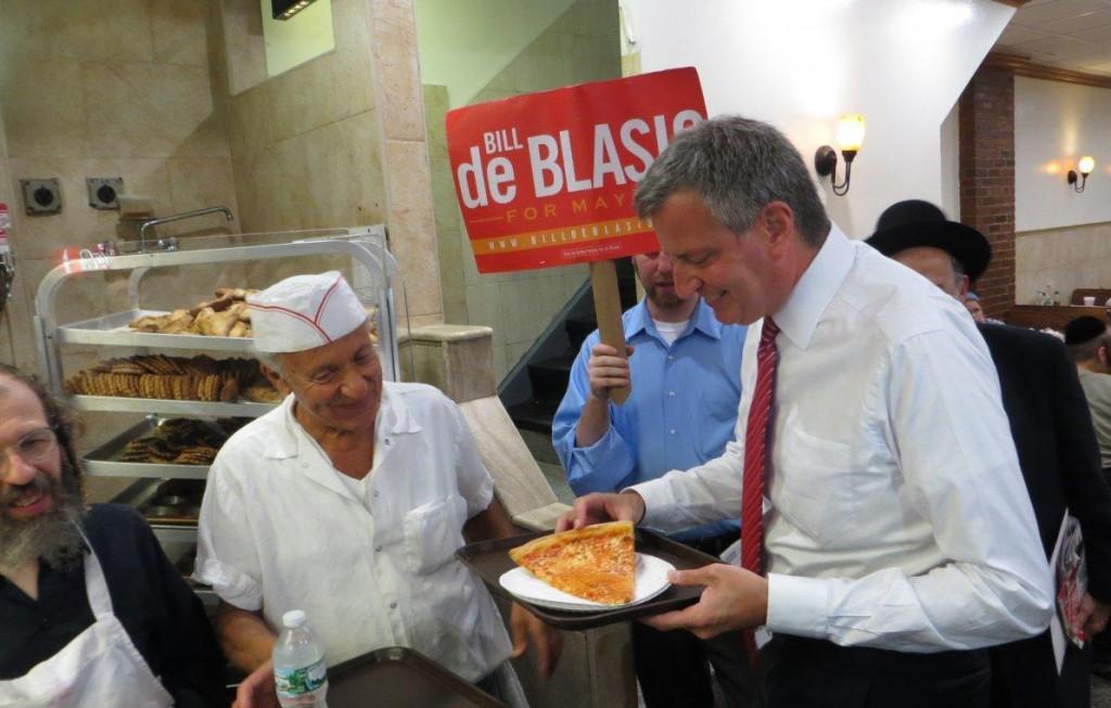 Bill de Blasio enjoys a slice of pizza at Amnon's in Boro Park Monday. (JDN)