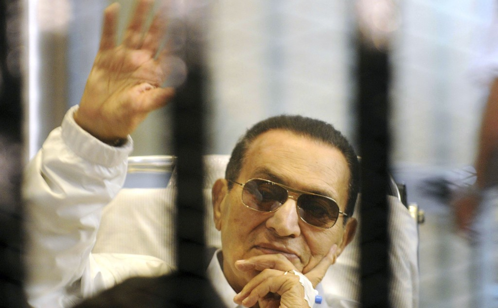 In this Saturday, April 13, 2013 file photo, former Egyptian President Hosni Mubarak waves to his supporters from behind bars as he attends a hearing in his retrial on appeal in Cairo, Egypt.  (AP Photo, File)