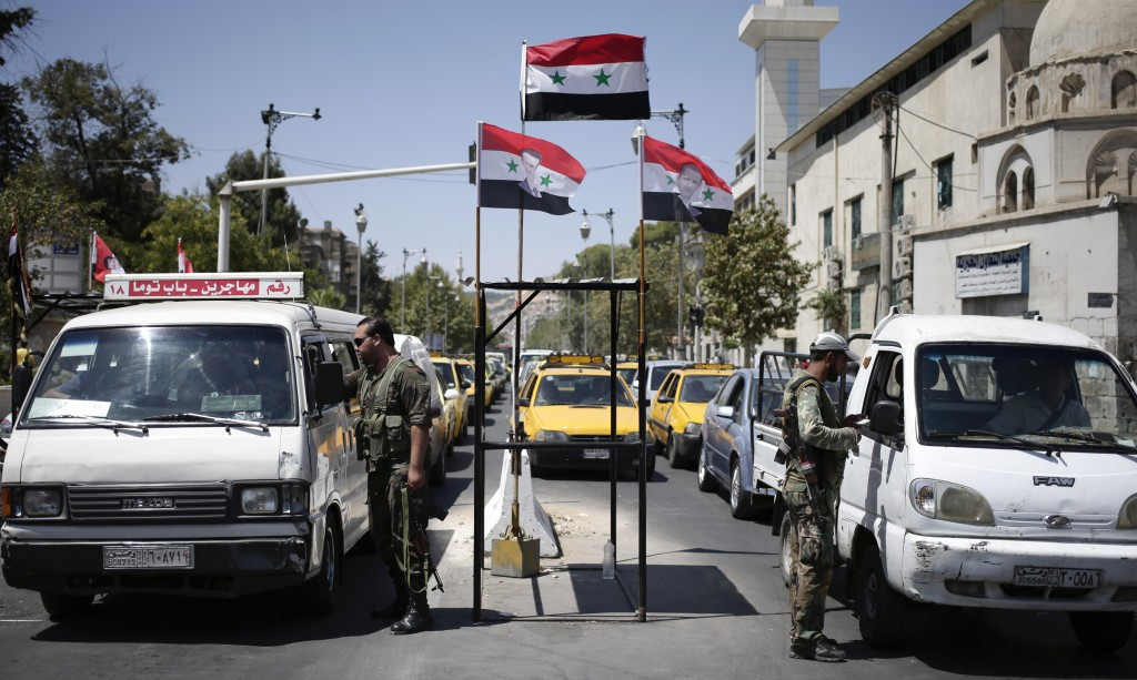 Syrian military soldiers check identifications at a checkpoint on Baghdad street, in Damascus, Syria, Wednesday, Aug. 21, 2013. (AP Photo/Hassan Ammar)